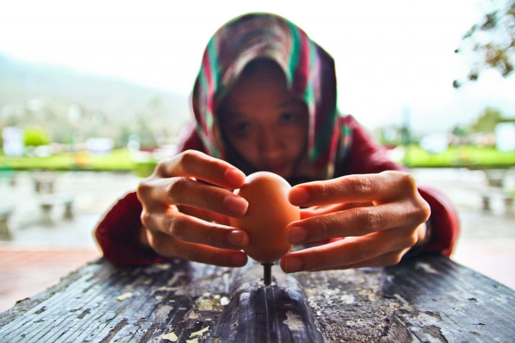 Mi pana coreana-boliviana Clara challenges the laws of gravity by balancing an egg on top the head of a nail at La Mitad Del Mundo, Pichincha, Ecuador